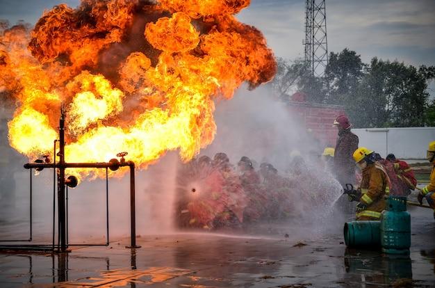 人々は水で消火器を練習しています。