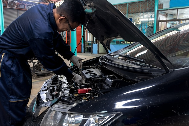 People are repair a car use a wrench and a screwdriver to work.