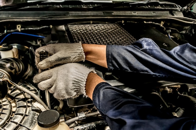 People are repair a car. use a wrench and a screwdriver to work.