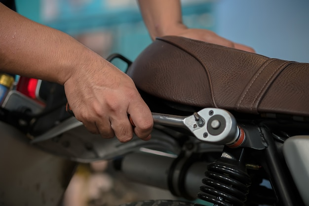 People are repairing a motorcycle use a wrench and a screwdriver to work.