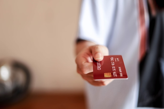 People are sending red credit cards forward, credit cards can be used to pay for goods and services at retail stores, restaurants, or online shopping. concept of using a credit card.