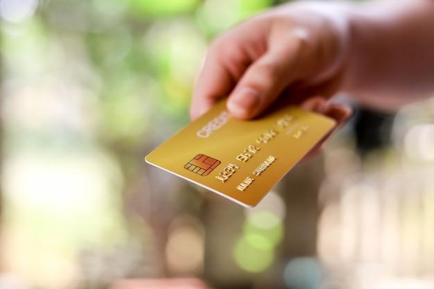 人々は赤いクレジットカードを転送しています。クレジットカードは、小売店、レストラン、またはオンラインショッピングでの商品やサービスの支払いに使用できます。クレジットカードを使用する概念。