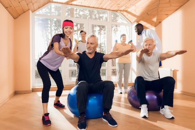Люди сидят на шарах для фитнеса.