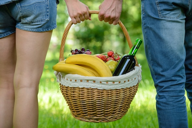 People are walk on picnic in park, holding a basket of food.