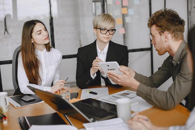 사람들이 프로젝트에 참여하고 있습니다. 남자와 여자 정장 테이블에 앉아. 기업인은 노트북을 사용합니다.