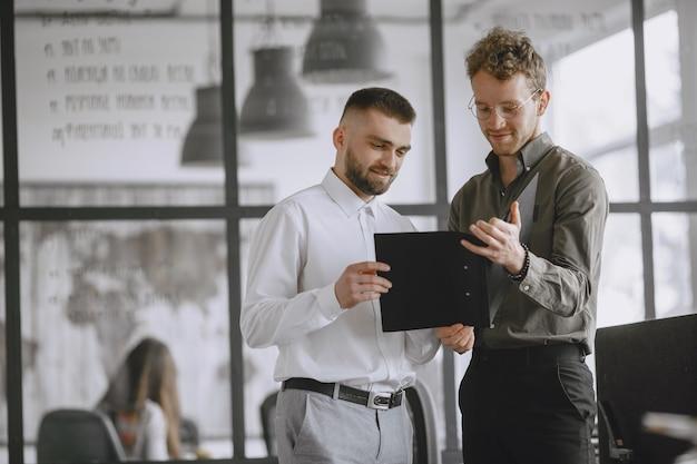 Над проектом работают люди. мужчин, занимающих папку. сотрудники в своем офисе.