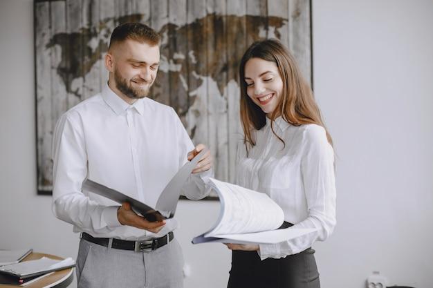 Le persone stanno lavorando al progetto. uomo e donna che tengono una cartella. dipendenti nel loro ufficio.