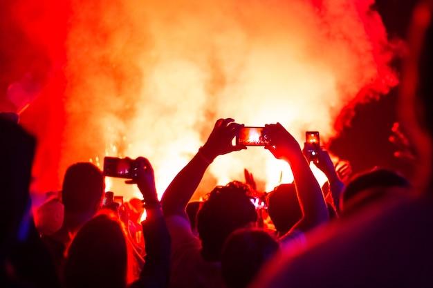 콘서트에서 사람들이 전화로 화재 쇼를 촬영합니다.