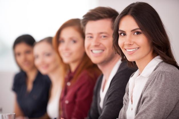 Люди на семинаре. привлекательная молодая женщина улыбается в камеру, в то время как другие люди сидят за ней в ряд