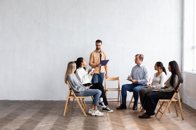 People attending a group therapy session with copy space