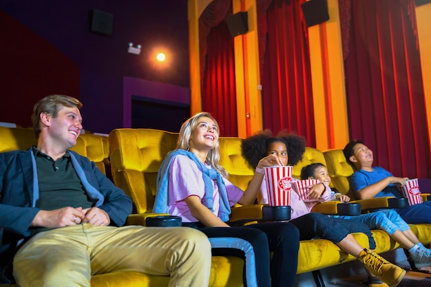 People audience with kid watching movie and feeling happy in a theater cinema.
