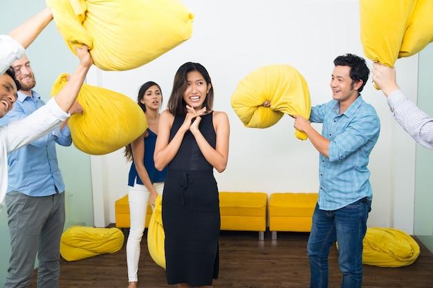 Люди избивают испуганного друга с подушками