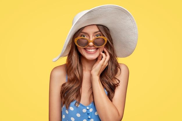 사람, 아름다움과 스타일 개념. 콘텐츠 유쾌한 유럽 여성은 흰색 모자, 물방울 무늬 드레스, 음영, 광범위하게 미소를 지으며 노란색 벽 위에 고립 된 리조트 장소에서 재현 된 기쁨을 누리고 있습니다.