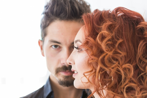 People and beauty concept - head shot portrait of couple with serious faces over white wall