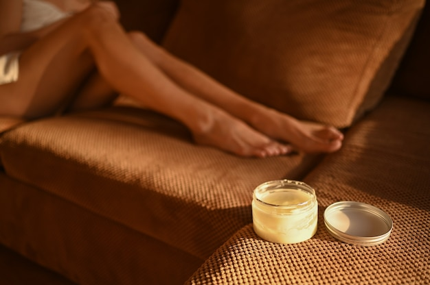 People beauty depilation epilation body care concept beautiful woman bare legs sitting on couch at