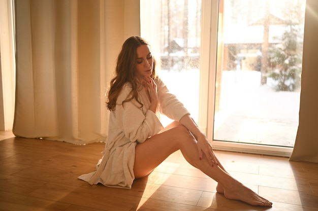 People beauty depilation epilation body care concept beautiful woman sitting on warm floor at home