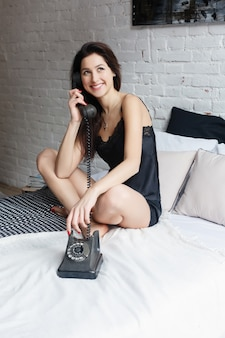 People, beauty, depilation, epilation and bodycare concept - beautiful woman with bare legs sitting on bed at home bedroom. happy young woman smiling in bed. girl talking on the phone in bed