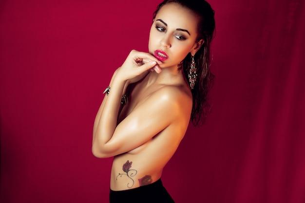 人、美しさ、ファッション、ライフスタイル、色のコンセプト-赤またはほのかな背景のスタジオで黒のハイランジェリーでヌードポーズをとる美しいセクシーなブルネットの女の子。広告スペース