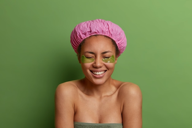 People, beauty and hygiene concept. joyful afro american woman wears bath cap, wrapped in towel, applies under eye patches after taking shower, cares about skin, poses against green wall