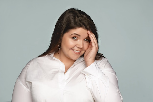 People, beauty and lifestyle concept. isolated shot of beautiful charming young brunette plus size woman wearing round earrings and formal shirt having shy timid look, hiding face behind her hand