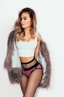 People, beauty and lifestyle concept - young beautiful brunette with curly hair in a beautiful fur coat and tights in the mesh and pink underwear a gray background. club style.