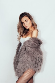 People, beauty and lifestyle concept - young beautiful brunette with curly hair in a beautiful fur coat and tights in the mesh and pink underwear a gray wall. club style.
