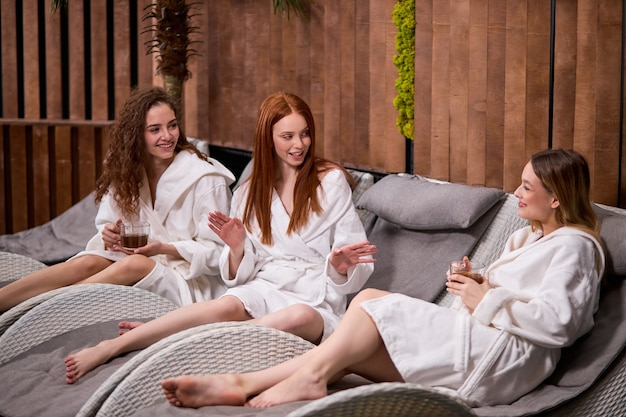 People beauty lifestyle holidays and relaxation concept  young caucasian women in white bathrobe sitting on chaiselongue