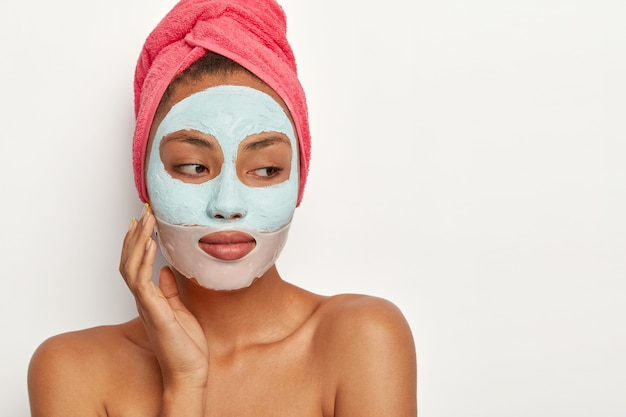 People, beauty, self care concept. thoughtful dark skinned woman touches cheek, applies clay mask and collagen patch around lips, wears towel on head
