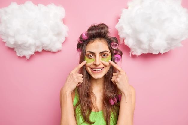 Persone concetto di bellezza e cura della pelle. la ragazza europea positiva indica le macchie di collagene sotto gli occhi, applica i bigodini sulla testa e viene sottoposta a trattamenti per il viso isolati su un muro rosa