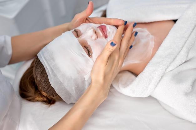 人、美容、スパ、美容、スキンケアのコンセプト。スパ美容室で美容師がフェイシャルマスクと布製マスクを適用しながら目を閉じて横たわっている美しい若い女性。コピースペース
