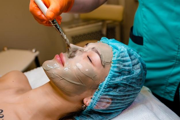 Люди, красота, спа, косметология и концепция ухода за кожей - крупным планом красивой молодой женщины, лежащей с закрытыми глазами, и косметолога, применяющего маску для лица кистью в спа
