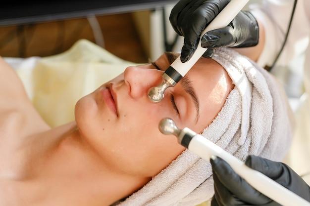 사람, 미용, 스파, 미용 및 기술 개념-미용사는 미용실에서 아름답고 젊은 남자의 얼굴 피부에 미세 전류 치료를합니다.