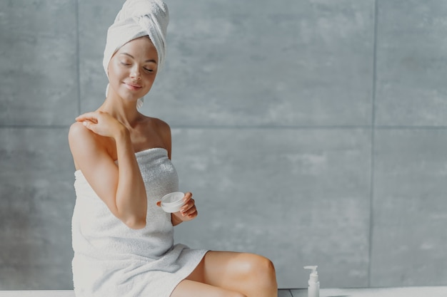 People, beauty, spa and cosmetology concept. relaxed young european female puts body cream, touches shoulder gently, wrapped in white soft towel, closes eyes with pleasure, poses against grey wall