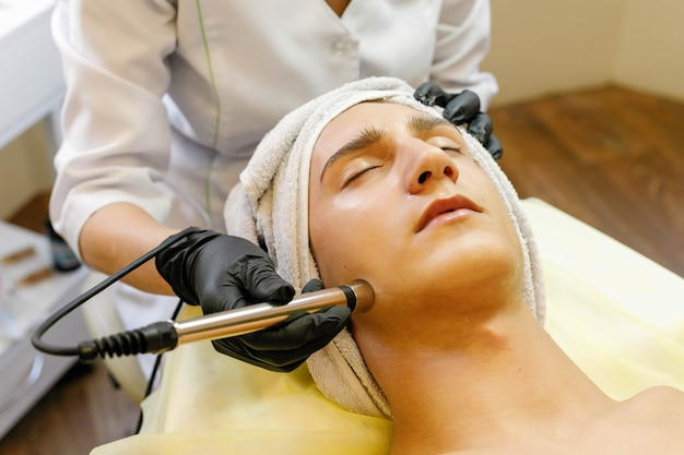 People, beauty, spa, cosmetology and technology concept - cosmetologist makes the procedure microcurrent therapy of the facial skin of a beautiful, young man in a beauty salon