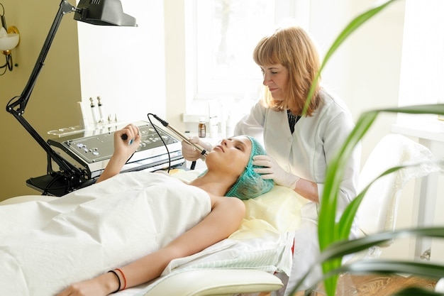 People, beauty, spa, cosmetology and technology concept - cosmetologist makes the procedure microcurrent therapy of the facial skin of a beautiful, young woman in a beauty salon