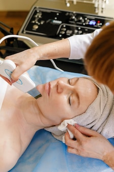 People, beauty, spa, cosmetology and technology concept - the cosmetologist makes the procedure ultrasonic face peeling of the facial skin of a beautiful, young woman in a beauty salon