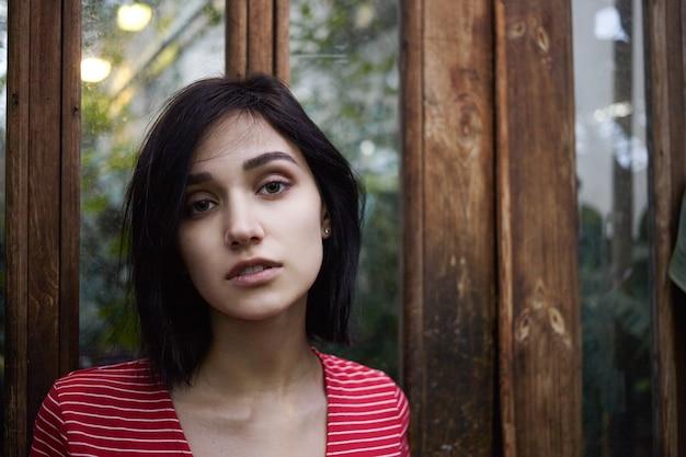 Люди, красота, стиль и концепция моды. изображение красивой девушки кавказской внешности, позирующей у деревянной стены с зеркальной поверхностью с копией пространства для молодой информации или рекламного контента