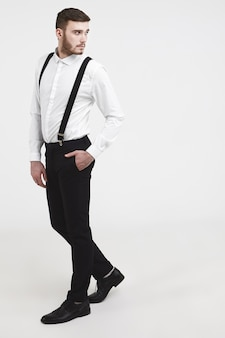 사람, 미용, 스타일, 패션, 남성복 및 액세서리. 스튜디오에서 유행 젊은 형태가 이루어지지 않은 남성 모델링의 세로 옆 사진, 세련된 바지 주머니에 손을 잡고 다시 찾고