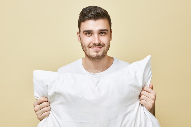 People, bedding and rest concept. portrait of attractive happy young male with stubble posing isolated holding white pillow going to sleep, with positive smile, saying good night