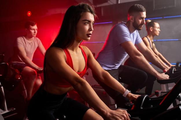 現代のジムでスピニングクラスで自転車に乗ったり、エアロバイクで運動したりする人々。エアロバイクでトレーニングする白人アスリートのグループ