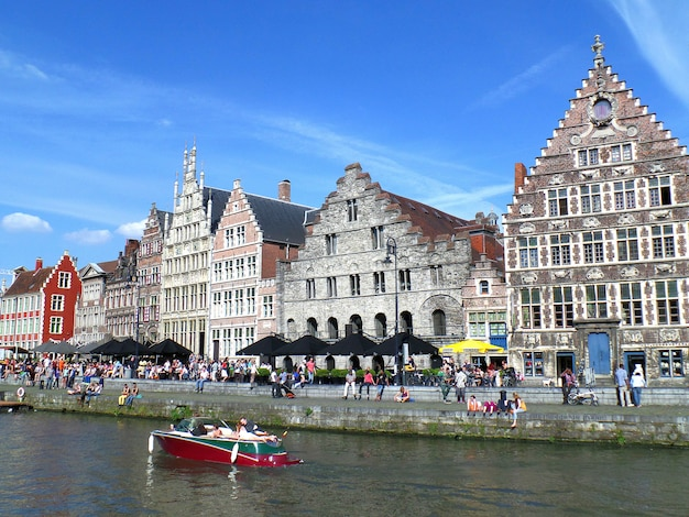 People boating and chilling out at riverside of ghent old town on the sunny sunday, ghent, belgium