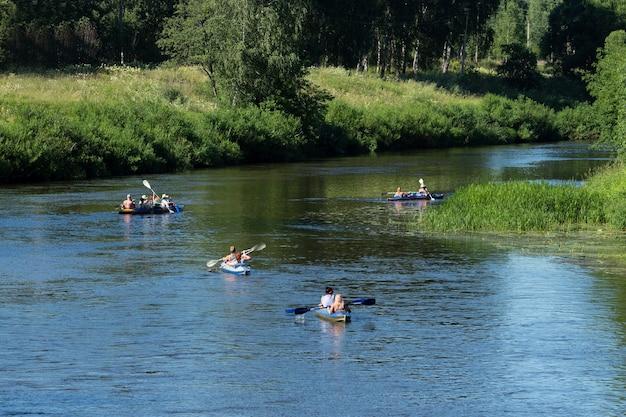 Люди катаются на лодке по реке, мирная природа в летний день