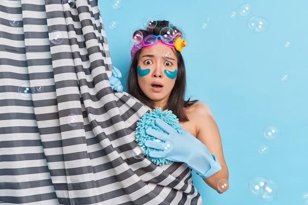 사람들의 바디 케어 및 샤워 개념. 겁에 질린 아시아 여성이 갑자기 욕실에 들어온 누군가가 미용을 받고 셀프 케어 트리트먼트를받으며 스펀지 비누 방울을 감싸고있는 것을보고 충격을 받았습니다.