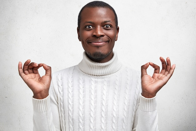 People, body language and positive emotions concept. happy handsome african american male stands in mudra pose, has delighted look