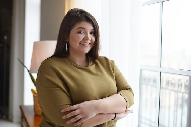 People, body positivity and lifestyle concept. indoor image of adorable overweight chubby young lady relaxing at home, standing at window, crossing arms on her chest, smiling broadly