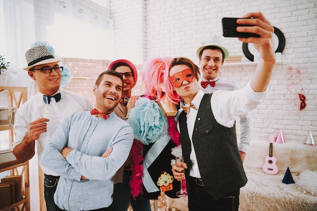 People in bow ties taking selfie on phone at party.