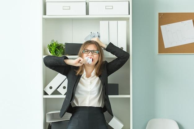 Концепция людей, бизнеса и эмоций - женщина с озадаченным выражением лица, одетая в костюм в офисе