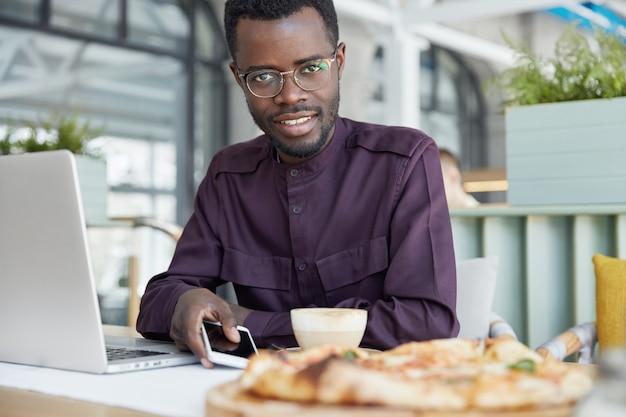 人、ビジネス、テクノロジーのコンセプト。フォーマルな服を着た暗い肌の喜ぶ若い男性、電話を待つ間現代のスマートフォンを保持