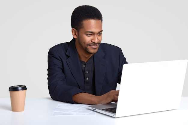 People, business and career concept. handsome dark skinned man dressed in formal clothes, works on laptop computer, surrounded with paper documents and takeaway coffee, isolated on white wall