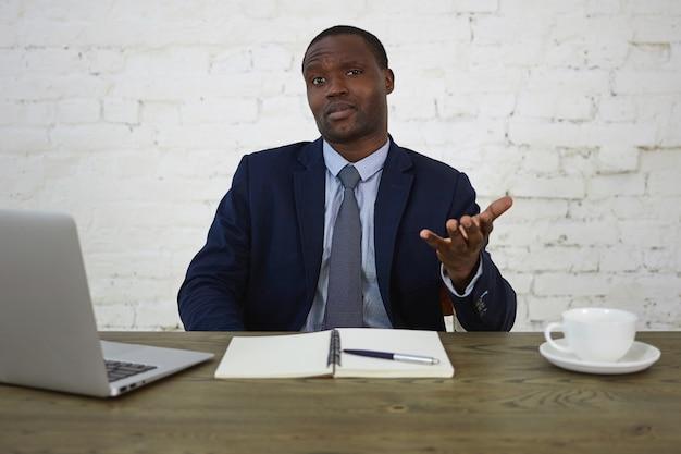 人、ビジネス、人間の表情と反応の概念。欲求不満の困惑した表情をして、憤慨して身振りで示すフォーマルなスーツを着ているハンサムな暗い肌の男性起業家の屋内ショット